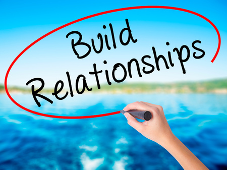 Woman Hand Writing Build Relationships on blank transparent board with a marker isolated over water background. Business concept. Stock Photo