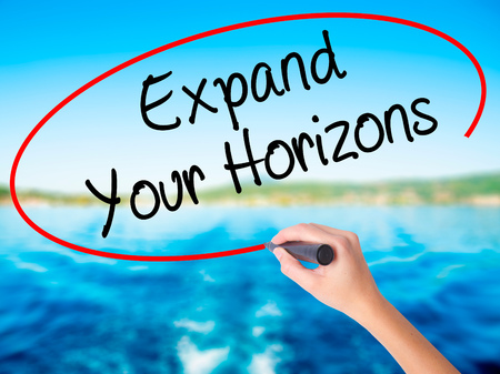 Woman Hand Writing  Expand Your Horizons  on blank transparent board with a marker isolated over water background. Business concept. Stock Photo