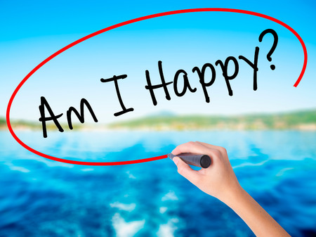 Woman Hand Writing Am I Happy? on blank transparent board with a marker isolated over water background. Business concept. Stock Photo Stock Photo
