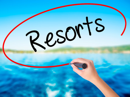 Woman Hand Writing Resorts  on blank transparent board with a marker isolated over water background. Business concept. Stock Photo