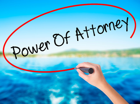 Woman Hand Writing Power Of Attorney on blank transparent board with a marker isolated over water background. Business concept. Stock Photo