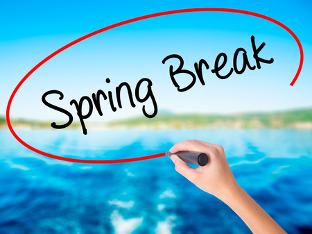 Woman Hand Writing Spring Break No on blank transparent board with a marker isolated over water background. Business concept. Stock Photo