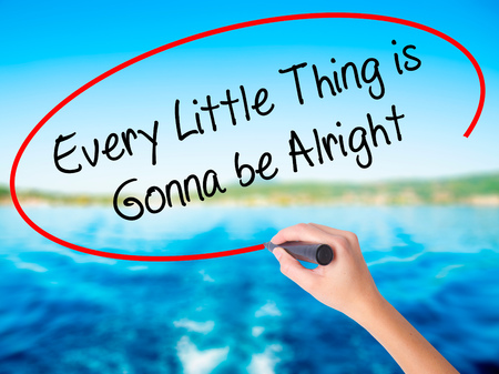 alright: Woman Hand Writing Every Little Thing is Gonna be Alright on blank transparent board with a marker isolated over water background. Business concept. Stock Photo Stock Photo