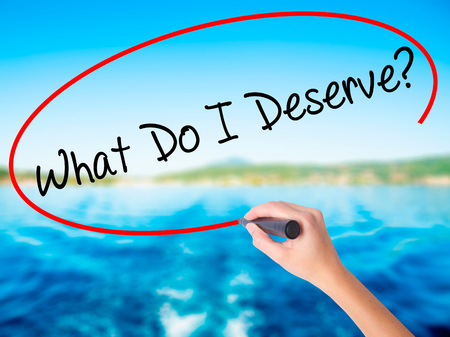 Woman Hand Writing What Do I Deserve? on blank transparent board with a marker isolated over water background. Business concept. Stock Photo
