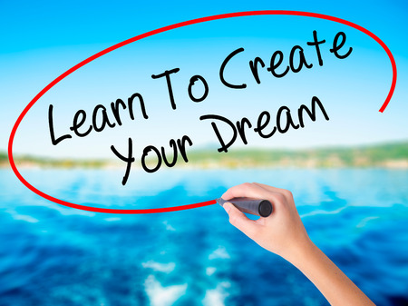 Woman Hand Writing Learn To Create Your Dream on blank transparent board with a marker isolated over water background. Business concept. Stock Photo Stock Photo