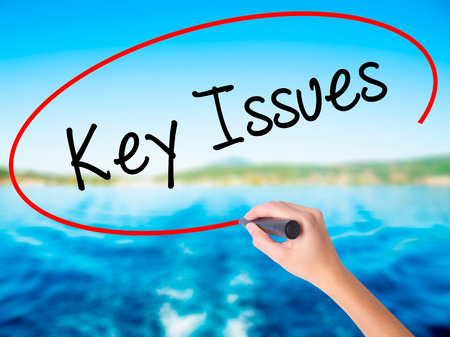 Woman Hand Writing Key Issues on blank transparent board with a marker isolated over water background. Business concept. Stock Photo Stock Photo