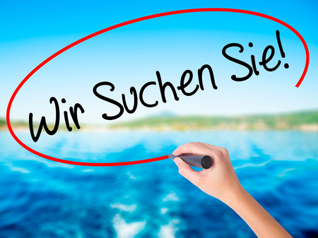 Woman Hand Writing Wir Suchen Sie! (Looking For You in German) with a marker over transparent board. Isolated on background. Business,  technology, internet concept. Stock Photo