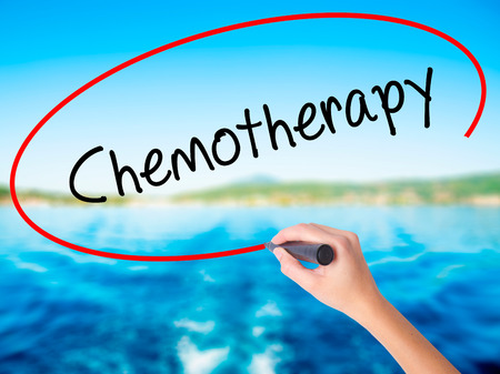 Woman Hand Writing Chemotherapy on blank transparent board with a marker isolated over water background. Business concept. Stock Photo Stock Photo