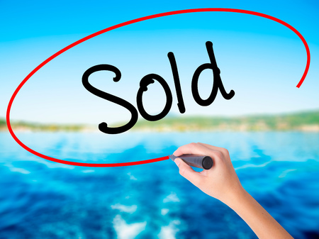 dream land: Woman Hand Writing Sold on blank transparent board with a marker isolated over water background. Business concept. Stock Photo