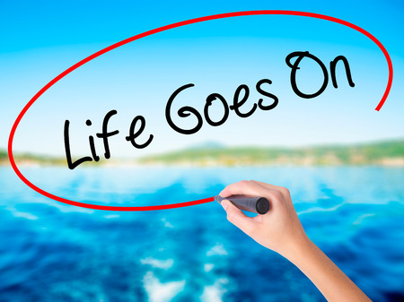 Woman Hand Writing Life Goes On on blank transparent board with a marker isolated over water background. Business concept. Stock Photo