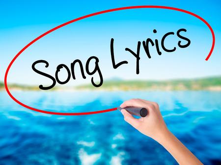 music lyrics: Las letras de canciones mano de la mujer escribiendo sobre la placa transparente en blanco con un marcador aislado sobre el fondo del agua. Concepto de negocio. Foto de stock Foto de archivo