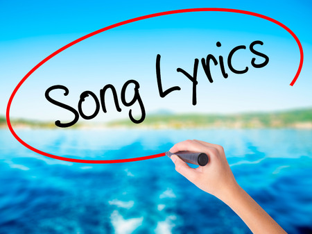 rhyme: Woman Hand Writing Song Lyrics on blank transparent board with a marker isolated over water background. Business concept. Stock Photo