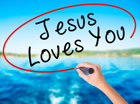 testament schreiben: Woman Hand Writing Jesus Loves You with a marker over transparent board. Isolated on white. Religion, technology, internet concept. Stock Image