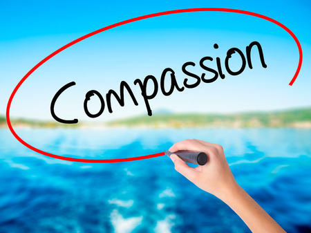 Woman Hand Writing Compassion on blank transparent board with a marker isolated over water background. Business concept. Stock Photo
