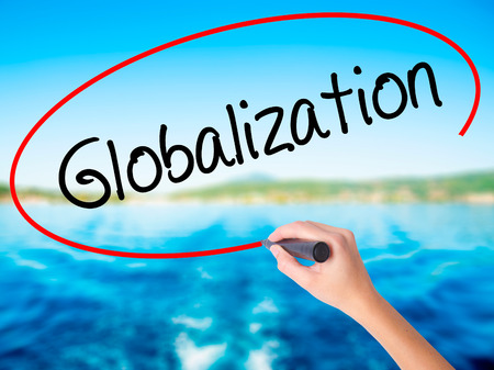 Woman Hand Writing Globalization on blank transparent board with a marker isolated over water background. Business concept. Stock Photo