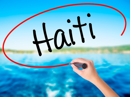 Woman Hand Writing Haiti on blank transparent board with a marker isolated over water background. Business concept. Stock Photo