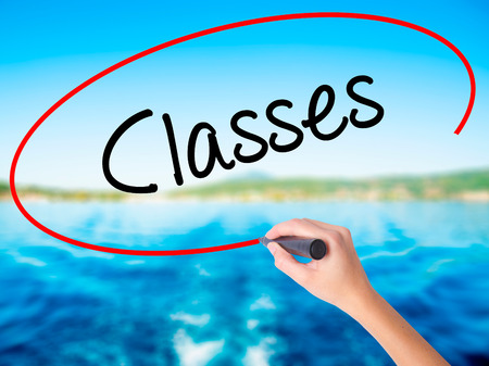 critical thinking: Woman Hand Writing Classes   on blank transparent board with a marker isolated over water background. Business concept. Stock Photo