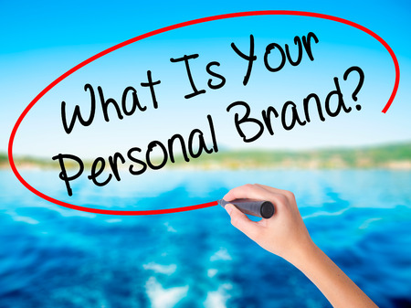 singularity: Woman Hand Writing What Is Your Personal Brand? on blank transparent board with a marker isolated over water background. Business concept. Stock Photo