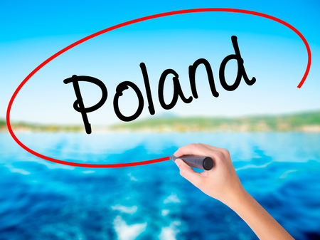 poznan: Woman Hand Writing Poland  on blank transparent board with a marker isolated over water background. Business concept. Stock Photo