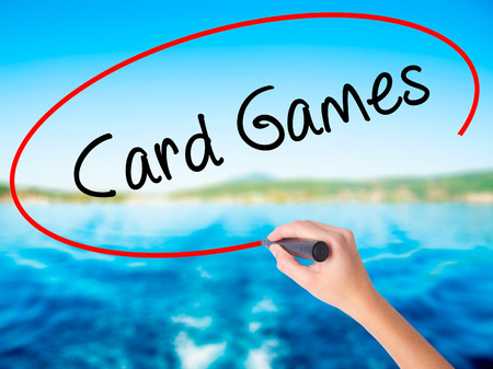 Woman Hand Writing Card Games on blank transparent board with a marker isolated over water background. Business concept. Stock Photo