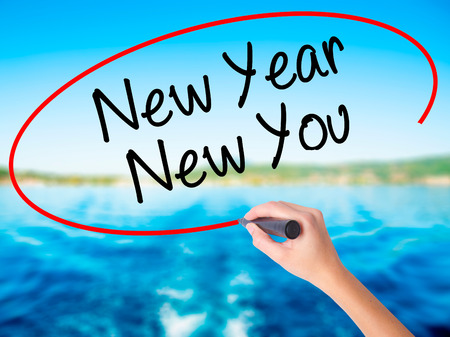 Woman Hand Writing New Year New You with a marker over transparent board. Isolated on city. Business, technology, internet concept. Stock Photo Stock Photo