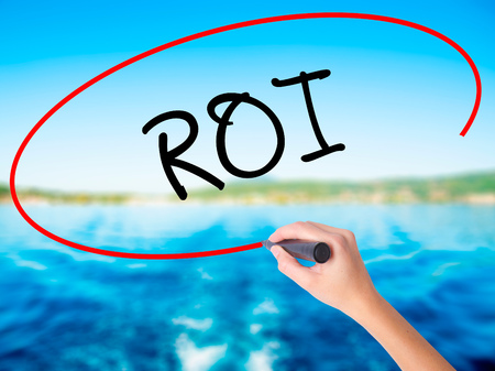 Woman Hand Writing ROI (Return on Investment)  on blank transparent board with a marker isolated over water background. Business concept. Stock Photo