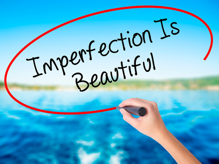 perfectionist: Woman Hand Writing Imperfection Is Beautiful on blank transparent board with a marker isolated over water background. Business concept. Stock Photo