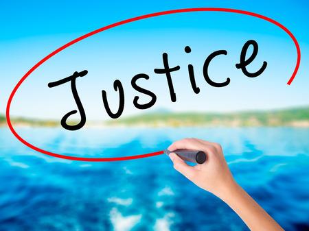 Mano de mujer escribiendo justicia en tablero transparente en blanco con un marcador aislado sobre fondo de agua. Concepto de negocio. Foto de stock