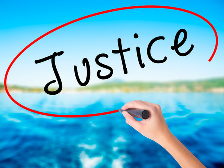 Woman Hand Writing Justice on blank transparent board with a marker isolated over water background. Business concept. Stock Photo Stock Photo