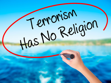 Woman Hand Writing Terrorism Has No Religion  on blank transparent board with a marker isolated over water background. Business concept. Stock Photo
