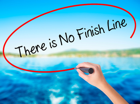 not ready: Woman Hand Writing There is No Finish Line on blank transparent board with a marker isolated over water background. Business concept. Stock Photo