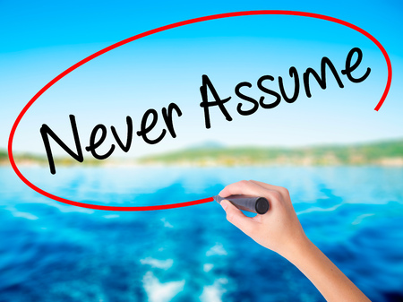assume: Woman Hand Writing Never Assume on blank transparent board with a marker isolated over water background. Business concept. Stock Photo