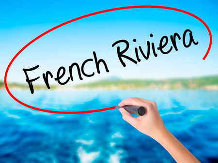 Woman Hand Writing French Riviera on blank transparent board with a marker isolated over water background. Business concept. Stock Photo