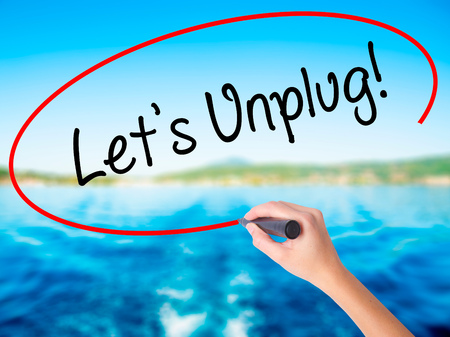 Woman Hand Writing Lets Unplug! on blank transparent board with a marker isolated over water background. Business concept. Stock Photo