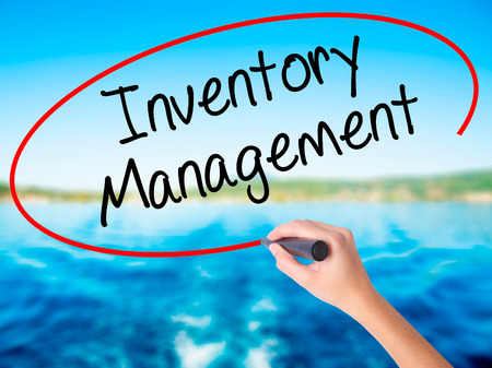 Woman Hand Writing Inventory Management on blank transparent board with a marker isolated over water background. Business concept. Stock Photo Stock Photo
