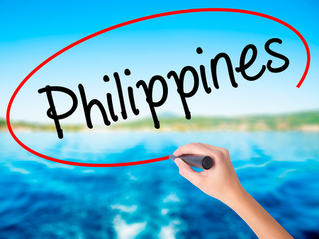 Woman Hand Writing Philippines on blank transparent board with a marker isolated over water background. Business concept. Stock Photo Stock Photo