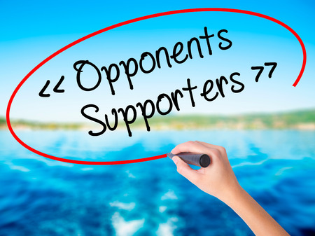 Woman Hand Writing Opponents - Supporters on blank transparent board with a marker isolated over water background. Business concept. Stock Photo Stock Photo