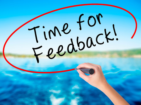 Woman Hand Writing Time for Feedback on blank transparent board with a marker isolated over water background. Business concept. Stock Photo