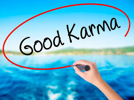 Woman Hand Writing  Good Karma on blank transparent board with a marker isolated over water background. Business concept. Stock Photo