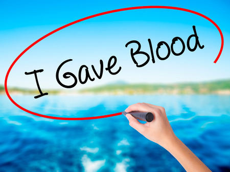 gave: Woman Hand Writing I Gave Blood on blank transparent board with a marker isolated over water background. Business concept. Stock Photo