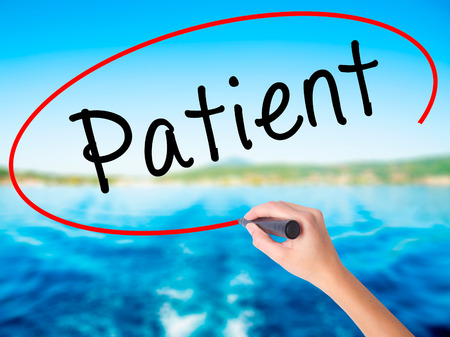 immediate: Woman Hand Writing Patient on blank transparent board with a marker isolated over water background. Business concept. Stock Photo