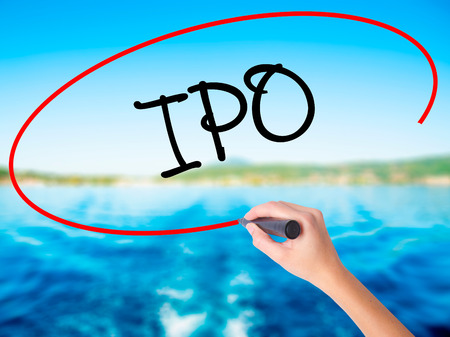Woman Hand Writing IPO (Initial Public Offering)   on blank transparent board with a marker isolated over water background. Business concept. Stock Photo
