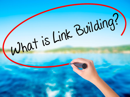 wiki: Woman Hand Writing What is Link Building? on blank transparent board with a marker isolated over water background. Business concept. Stock Photo