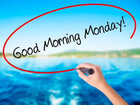 Woman Hand Writing Good Morning Monday! on blank transparent board with a marker isolated over water background. Business concept. Stock Photo