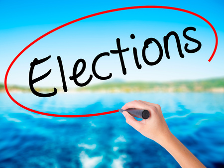 Woman Hand Writing Elections on blank transparent board with a marker isolated over water background. Business concept. Stock Photo Stock Photo