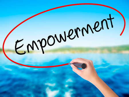 Woman Hand Writing Empowerment on blank transparent board with a marker isolated over water background. Business concept. Stock Photo