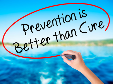 Woman Hand Writing Prevention is Better than Cure on blank transparent board with a marker isolated over water background. Business concept. Stock Photo