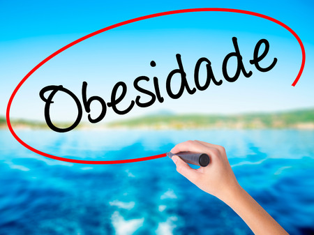 Woman Hand Writing Obesidade (Obesity in Portuguese)  on blank transparent board with a marker isolated over water background. Business concept. Stock Photo