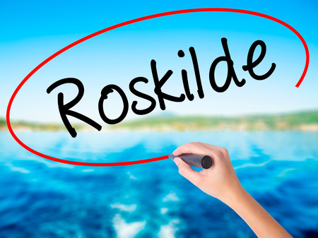 Woman Hand Writing Roskilde  on blank transparent board with a marker isolated over water background. Business concept. Stock Photo