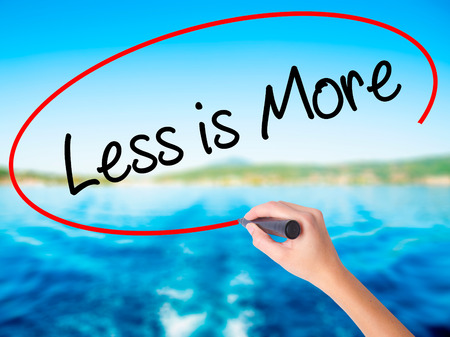 work less: Woman Hand Writing Less is More on blank transparent board with a marker isolated over water background. Business concept. Stock Photo